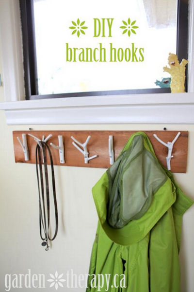 Garden twigs painted white make a great coat hook display.
