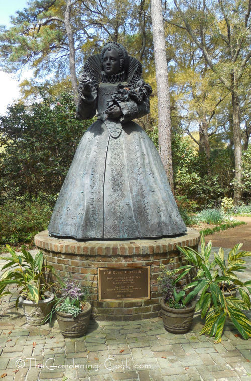 Queen Elizabeth I stands at the beginning of the garden paths.