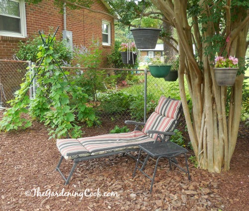 Lounging seating area with hanging baskets in the trees and a wind chime.