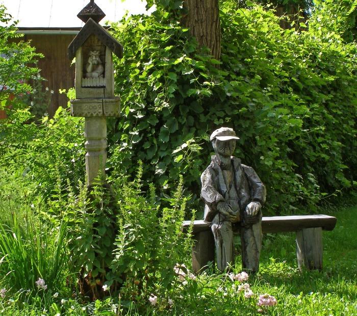 Carved figure on a log garden bench