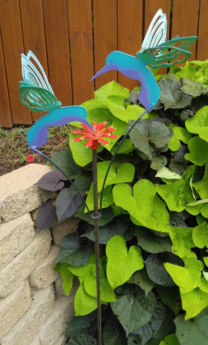 Metal yard art hunningbirds with tiny hummingbird feeder