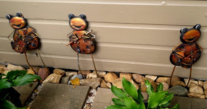 Creative Metal Yard Art Frogs add a whimsical greeting to the front door of the cottage