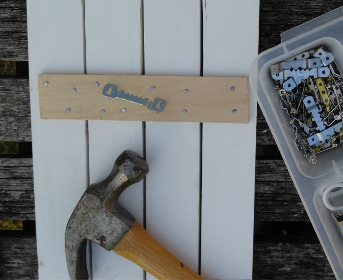 Attach a metal saw tooth picture hanger in place.