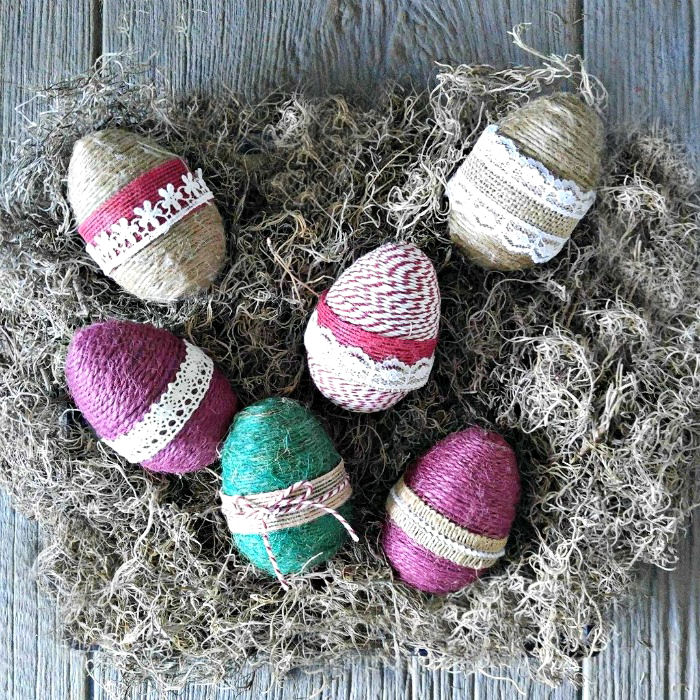 These rope wrapped eggs with burlap ribbon trim look great in a bird's nest.