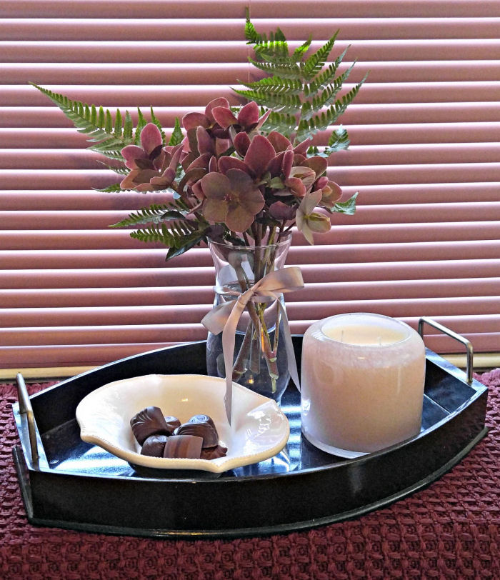 Pink Alassa candle on a tray with chocolates and Monrovia hellaborus flowers