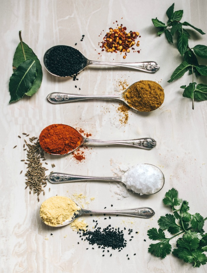 spices on spoons with fresh herbs