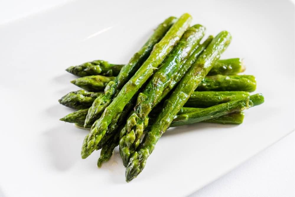 Roasted asparagus spearson a white plate.