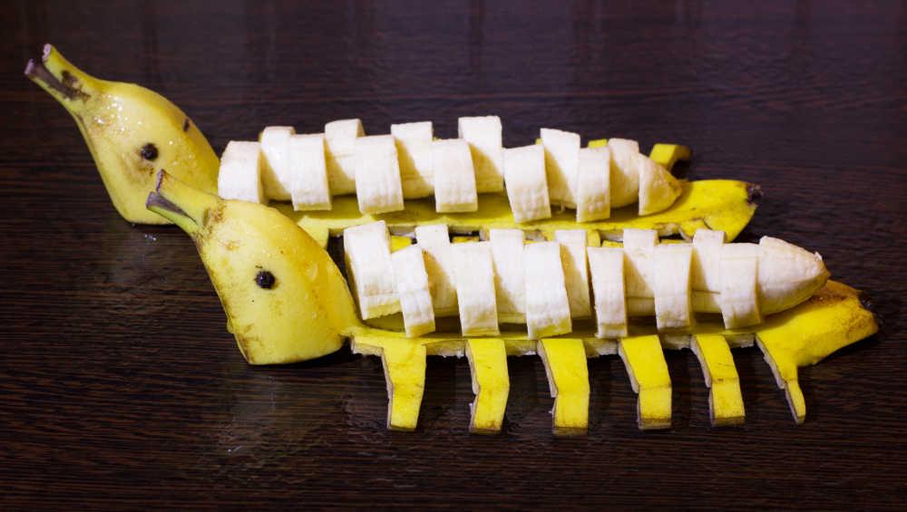Bananas sliced and sitting on banana skins shaped like ducks.