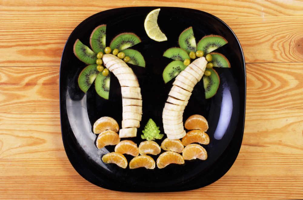 Banana carving scene: Bananas, kiwi fruit and oranges in a palm tree scene.