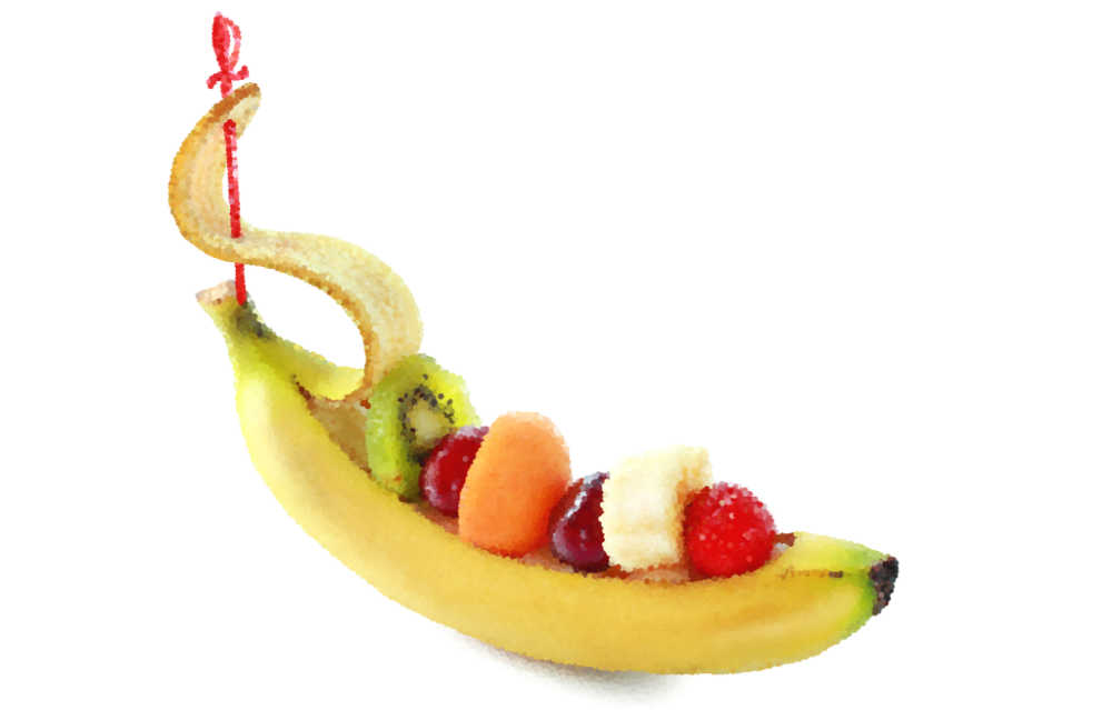 Banana scooped out and filled with fruit to make a ship.