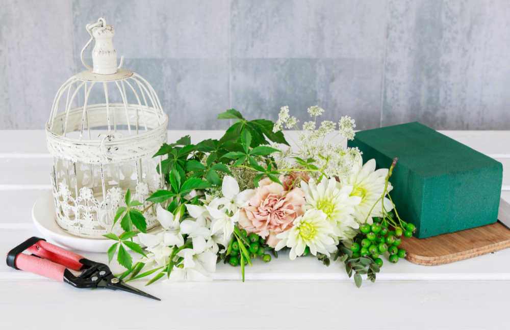 Supplies for arranging silk flowers in a bird cage.
