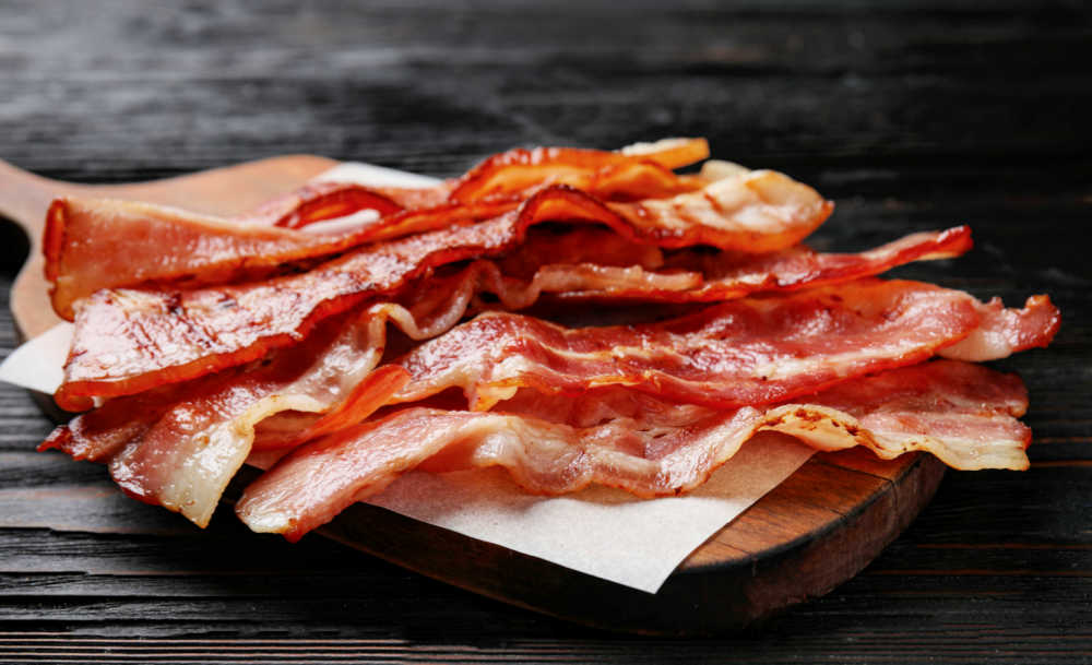 Cooked bacon on a piece of parchment paper.