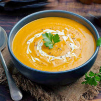 Curried carrot soup in a bowl with parsley.