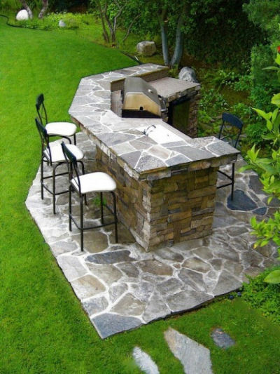 Outdoor kitchen with flagstone and stacked stone.