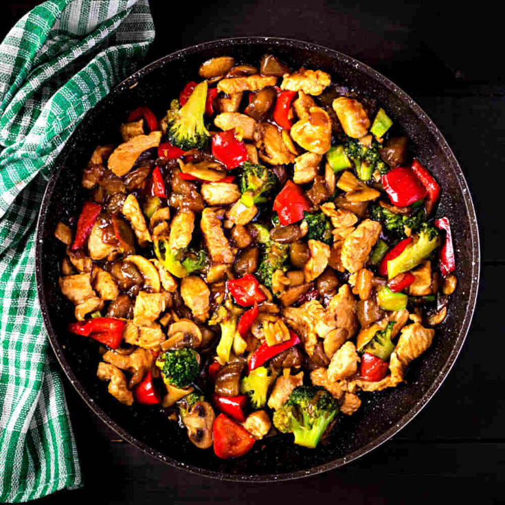 Stir fry in a bowl on a black background with checked green towel.