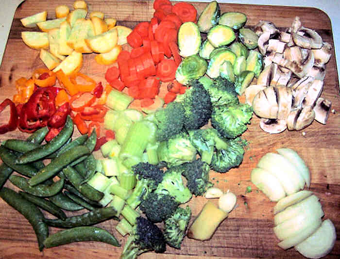 Broccoli, peppers, peas, onions and other vegetables on a cutting board.