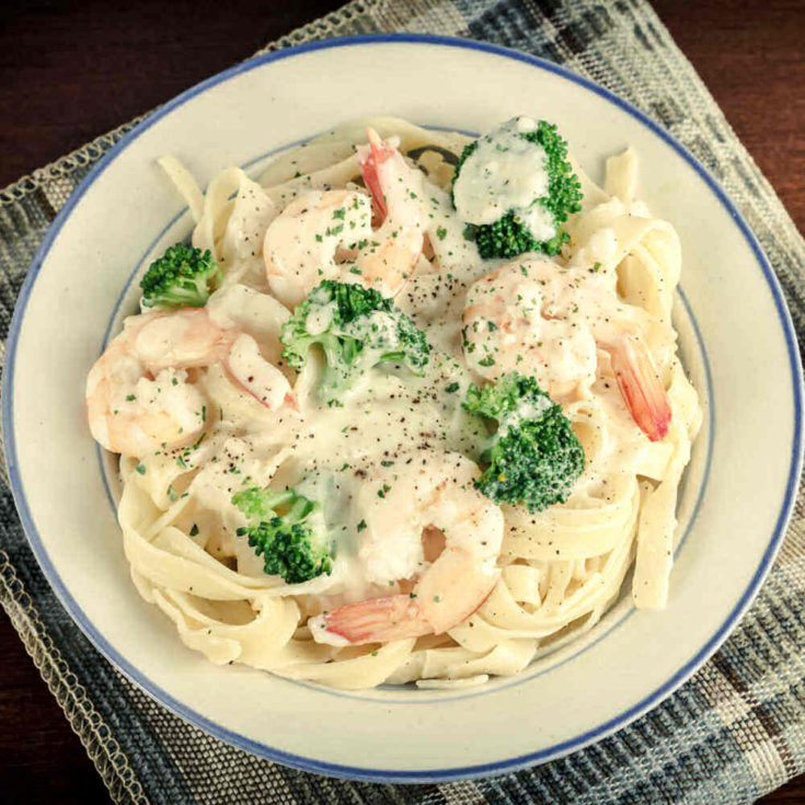 Shrimp pasta with broccoli in a blue and white bowl.