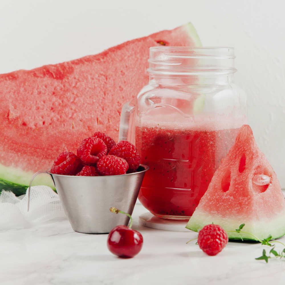 Raspberries and watermelon with Mason jar of juice.