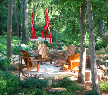 Rustic patio with lush trees around it.