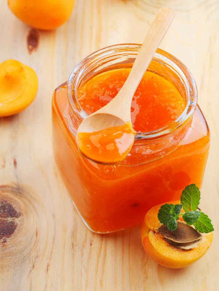 apricots and apricot jam in a jar with a spoon.
