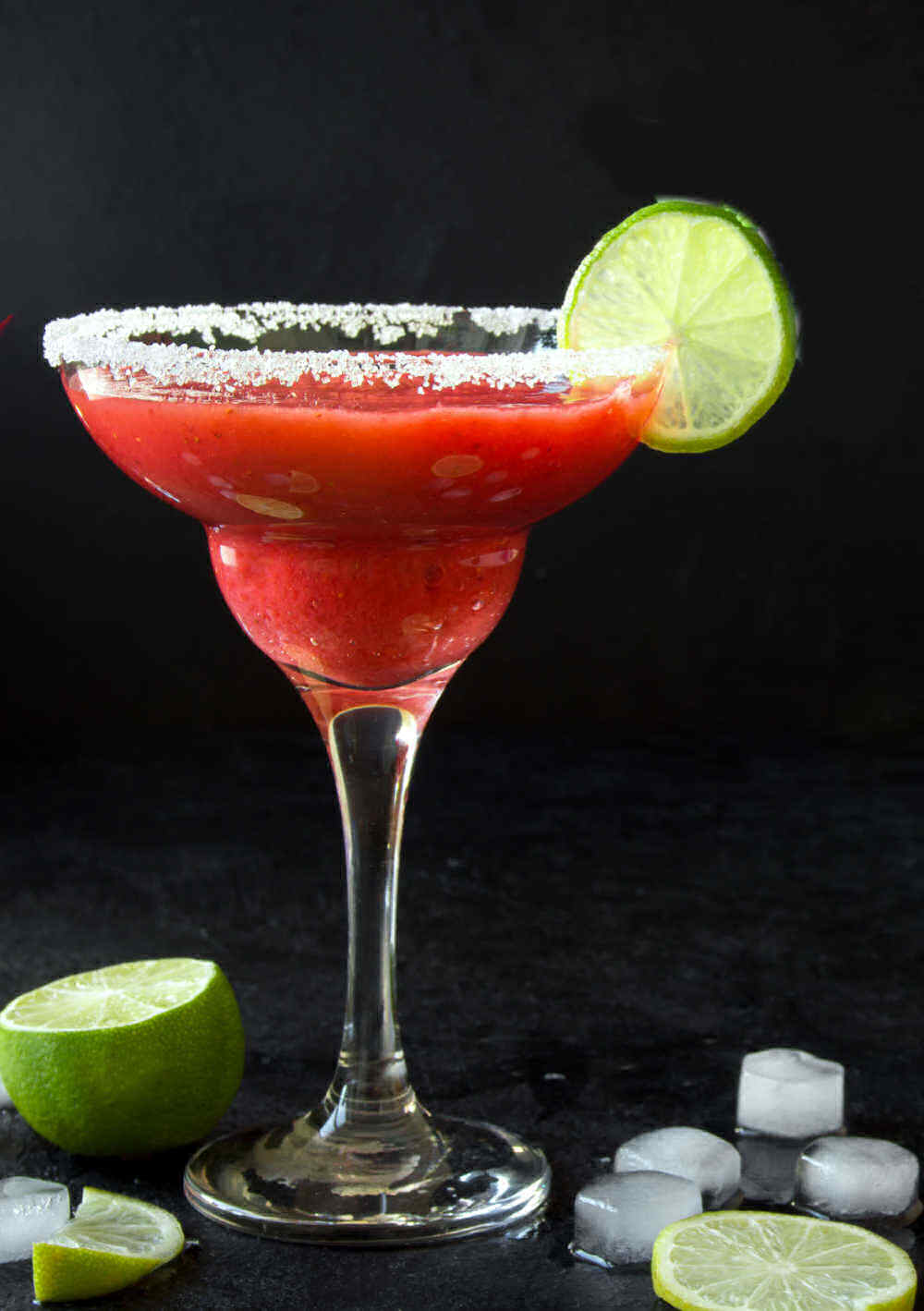 Slushy strawberry drink in a martini glass with salt and lime.