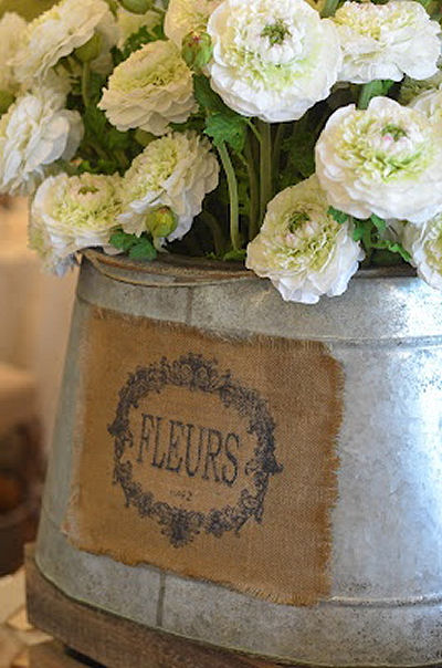 Galvanized bucket with burlap, perfect for Spring flowers on a farmhouse porch!