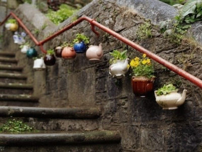 Teapots as planters and hung on rails. Great street art.