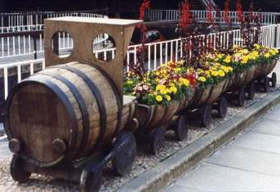 Whiskey barrels transformed into train and then planted.
