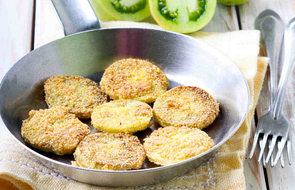 Fried green tomatoes in a frying pan.
