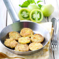 Green tomatoes and fried green tomatoes in a frying pan with a fork.