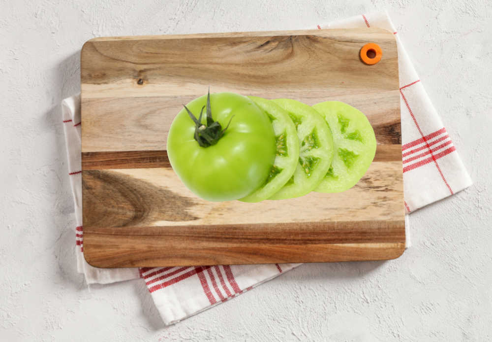 Green tomato slices on a cutting board.