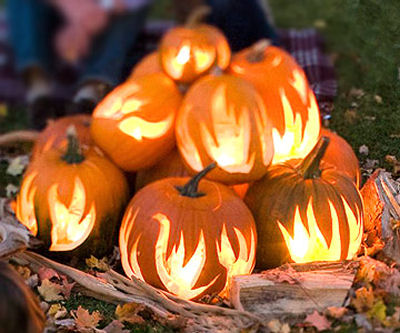 Flame Pumpkins in a log setting for a perfect fire scene.