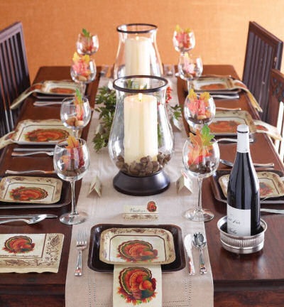 Thanksgiving tablescape with colorful napkins and leaves in wine glasses