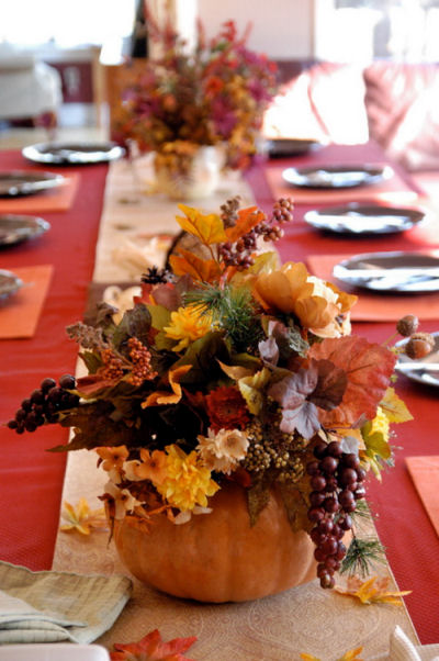 Table centerpiece with fall greenery in hollowed out pumpkins