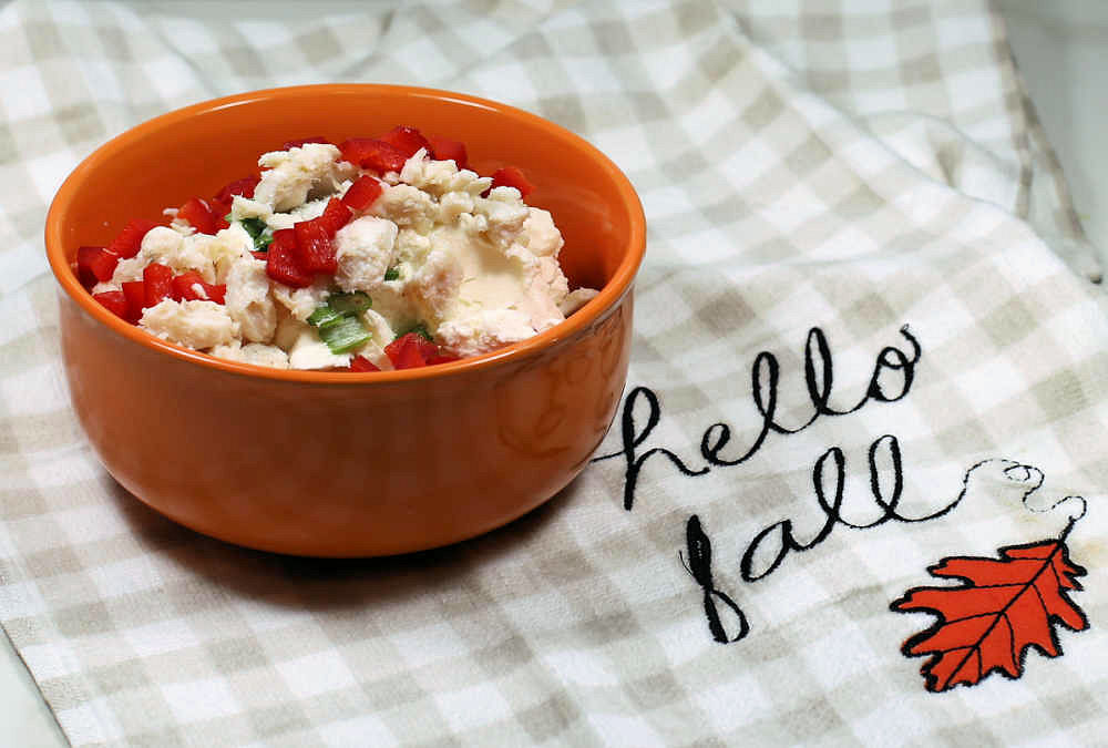 Orange bowl with cream cheese, red peppers, onions and crabmeat and tea towel with words Hello fall.