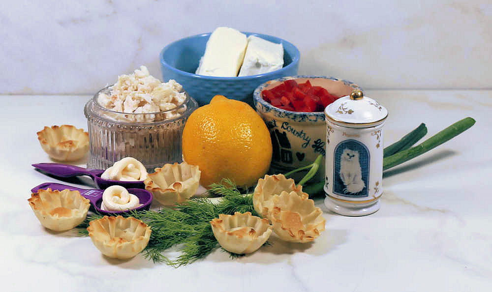 Cream cheese, lemon, red pepper, paprika, horseradish sauce, phyllo cups, dill, onion and crab meat on a counter.
