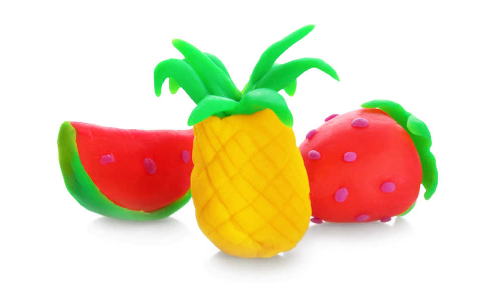 Watermelon, pineapple and strawberries made of out playdough.