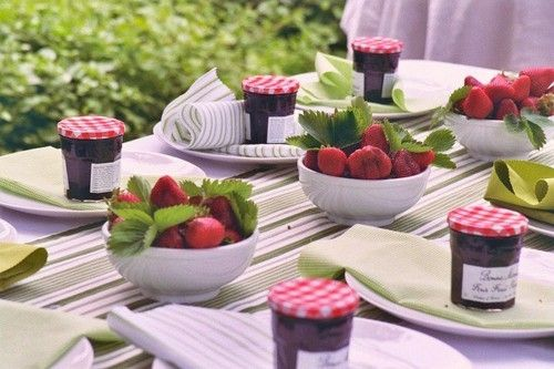 Strawberry themed tablescape with bowls of strawberries and jars of jam.