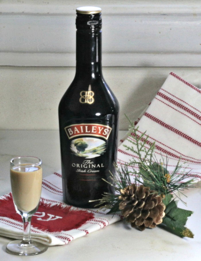 Shot of Bailey's Irish Cream with a bottle, towel and pine cone.