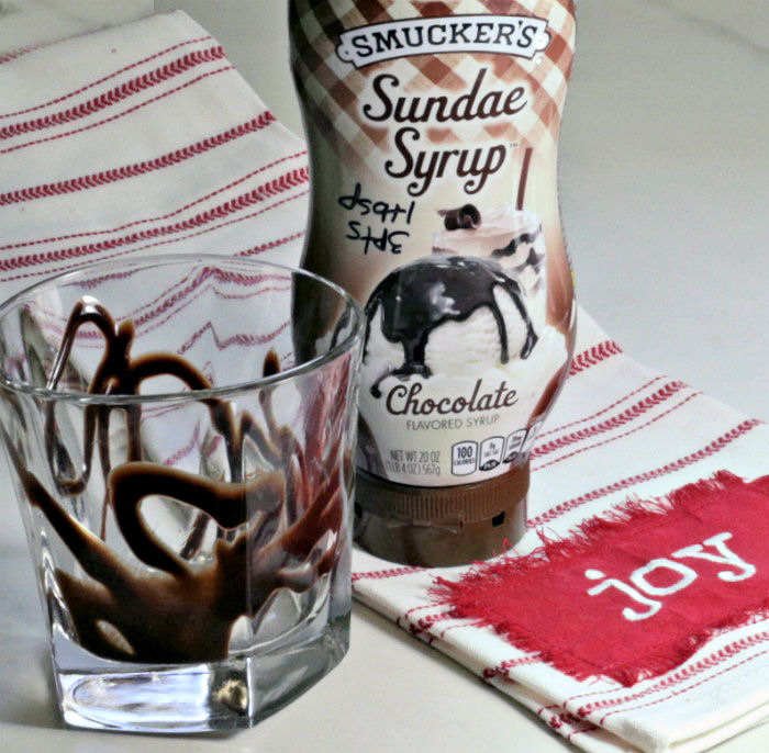 drizzled glass with chocolate syrup and Joy towel.
