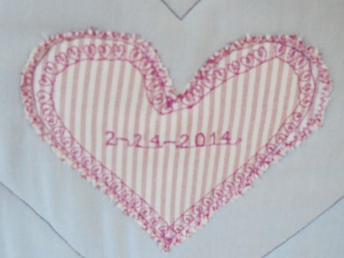 The date of death is stiched on to heart shaped fabric.