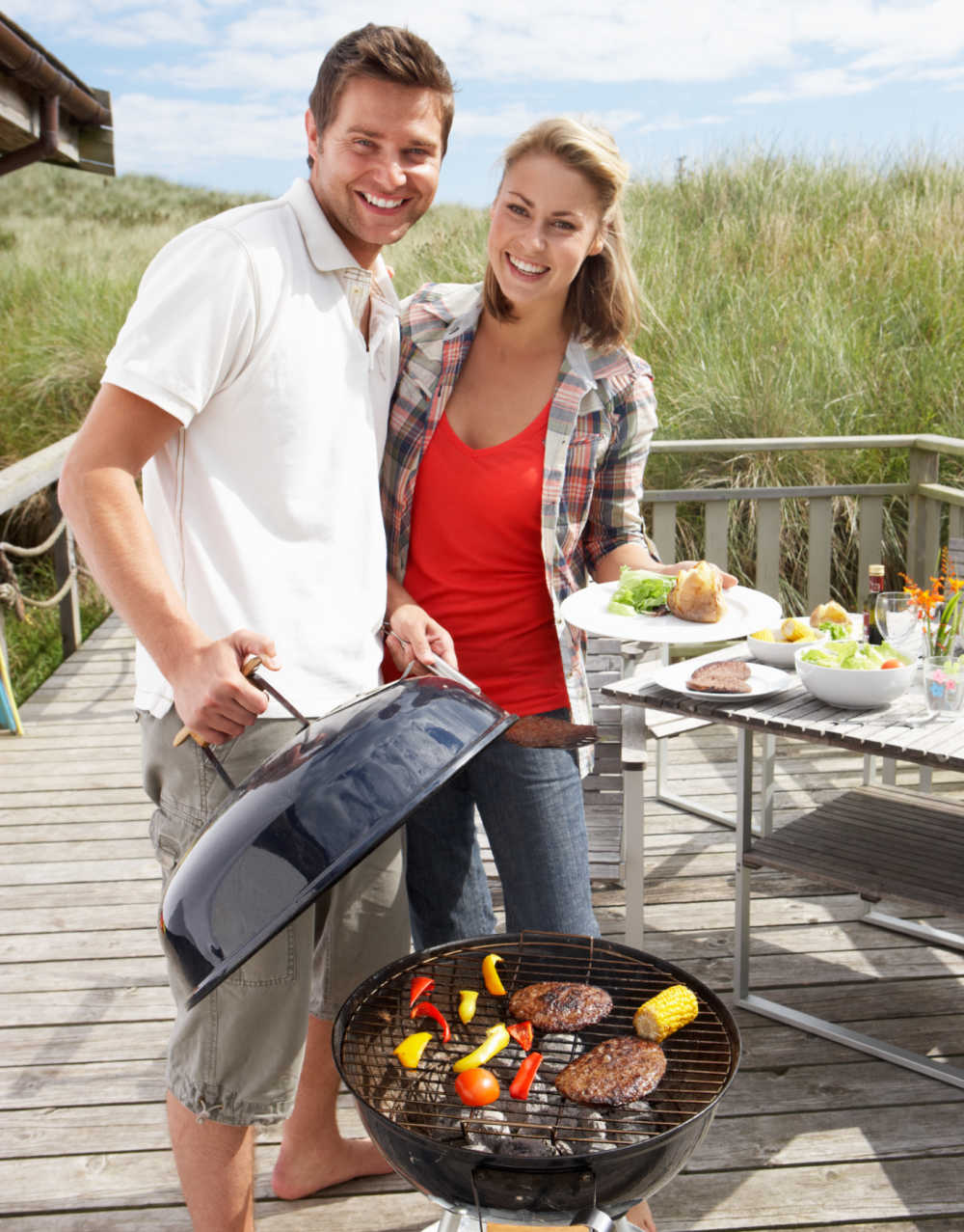 Man and woman with food at a BBQ party.