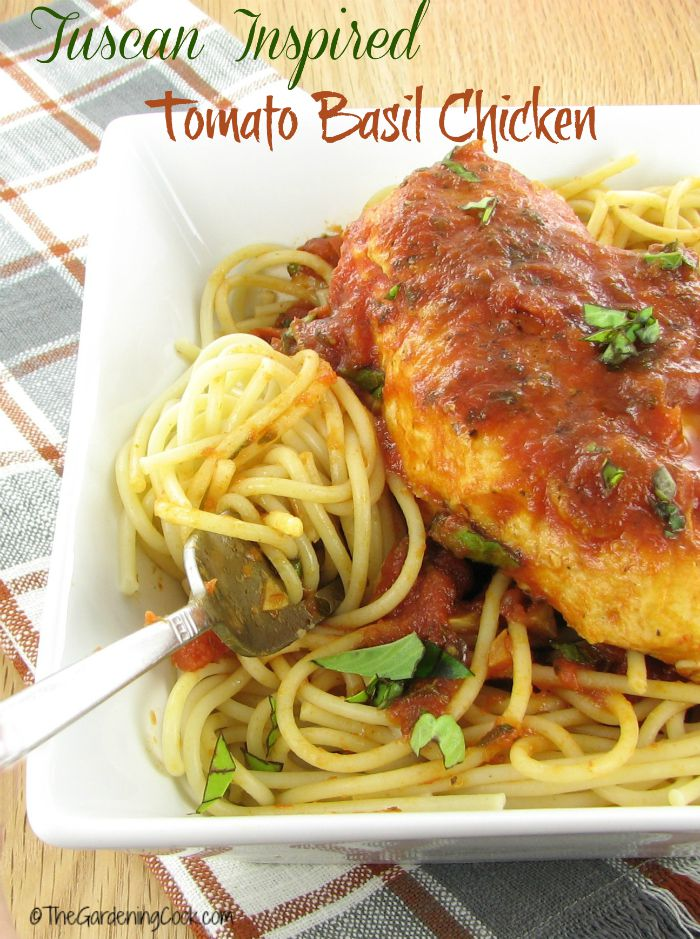 Chicken with sauce and spaghetti on a white plate with words readingTuscan inspired Tomato basil chicken..