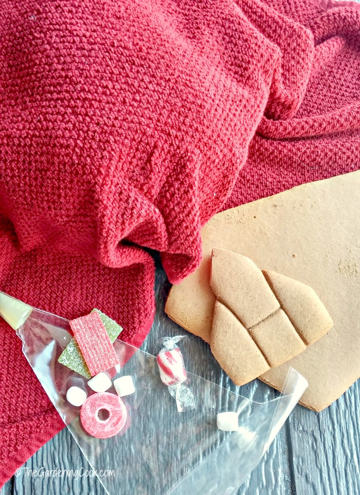 gingerbread pieces, candy, icing bag and clean tea towel.