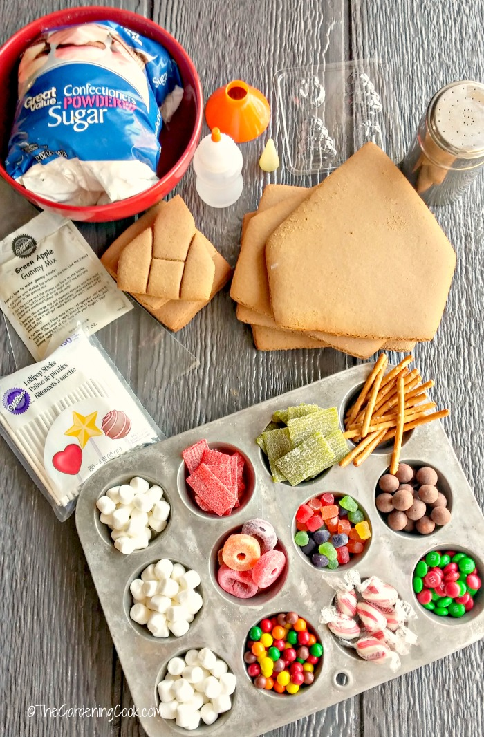 Candy in muffin tins, gingerbread house pieces, sugar and other supplies for making your own gingerbread house.