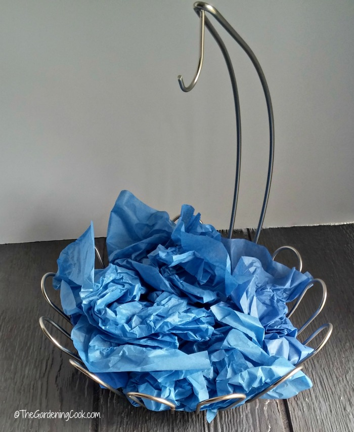 Add height to the basket with crumpled tissue paper
