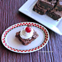 Brownie on a checked plate with whip cream and a cherry, near a plate of brownies.