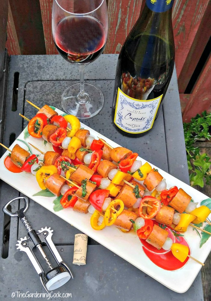 Cajun style Andouille sausage kebabs with wine in a bottle and glass and corkscew.