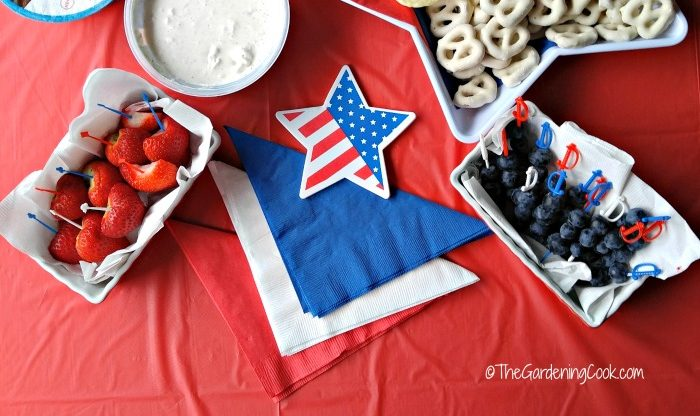 Strawberries, dip, yogurt pretzels and blueberries with flag star and red white and blue napkins.