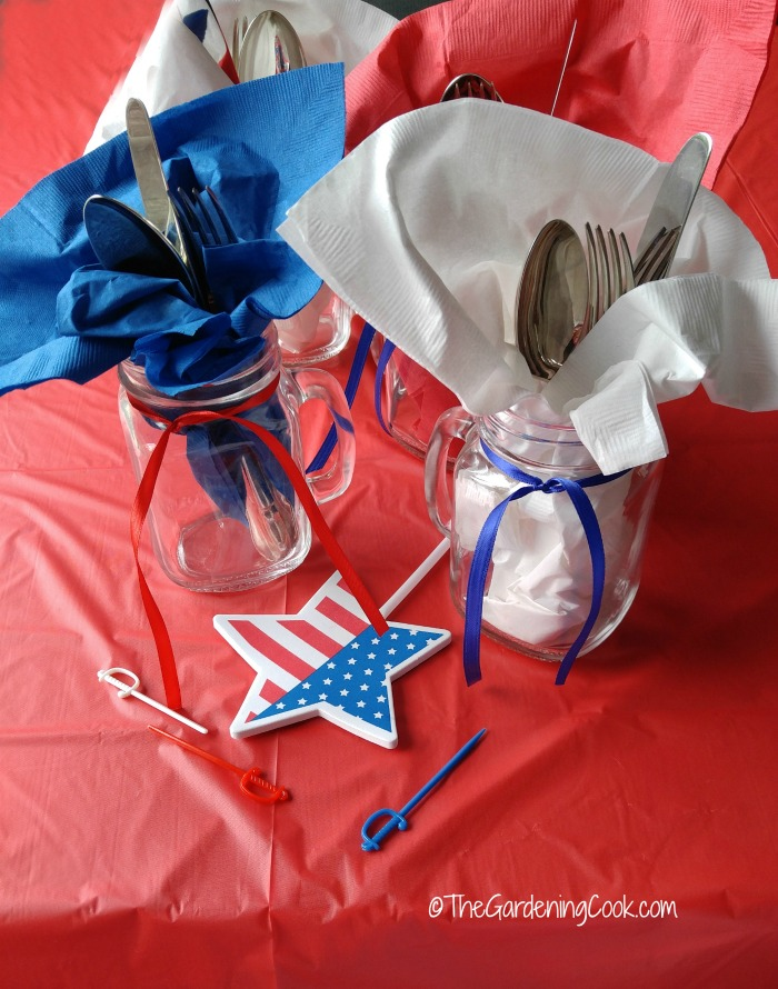 Patiotic Mason Jar cutlery holders with blue and white napkins, red and blue ribbons and flag stars on a red table cloth.